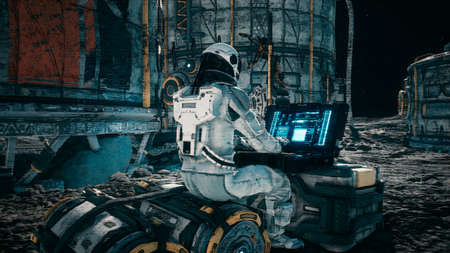 An astronaut works on his laptop at a space base on one of the new planets. 3D Rendering.