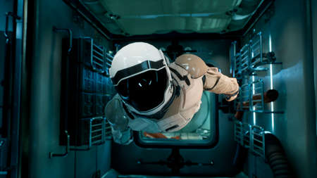 An astronaut in zero gravity checks the module of his spaceship. 3D Rendering. Imagens