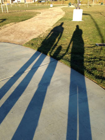 shadow: Shadow of family holding hands at the park.
