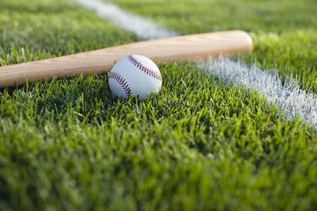 A selective focus view of a baseball bat and ball on the grass near a field stripe