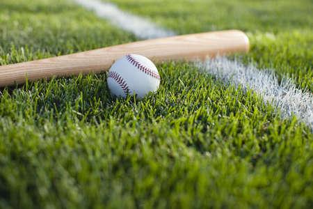 campo de beisbol: Una vista de enfoque selectivo de un bate de béisbol y bola en el césped cerca de una raya campo