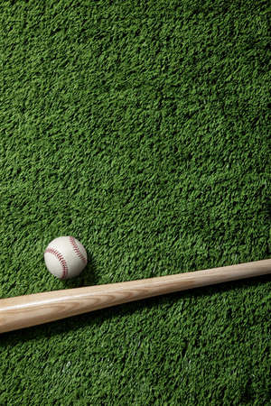 Overhead view of a baseball and bat on green artificial turf Stock Photo