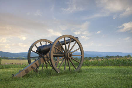 A cannon at Antietam  Sharpsburg  Battlefield in Maryland with the fence of Bloody Lane photo