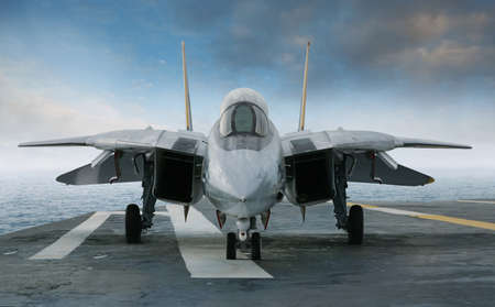Un avión de combate en una cubierta portaaviones bajo un cielo azul y las nubes visto desde el frente