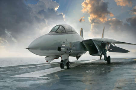 An jet fighter sits on the deck of an aircraft carrier deck beneath dramatic clouds