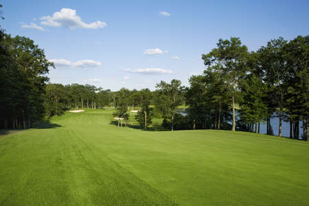 Beautiful golf fairway lined with trees alongside a lake leading to green