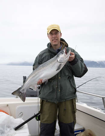 A happy fisherman in Alaska holds up a freshly caught silver salmon Stock Photo - 15919480