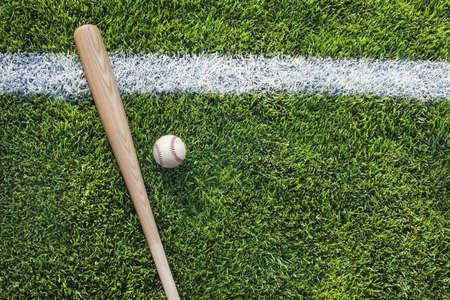 campo de beisbol: B�isbol y palo en campo de hierba con la raya