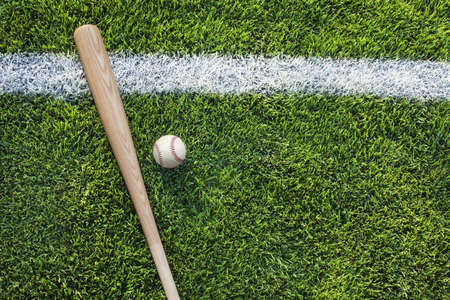Baseball and bat on grass field with stripe Фото со стока