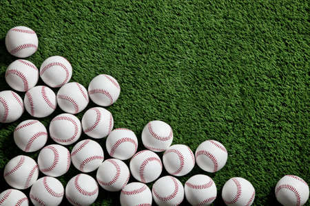 Several baseballs in the corner of a green turf background viewed from above Stock Photo