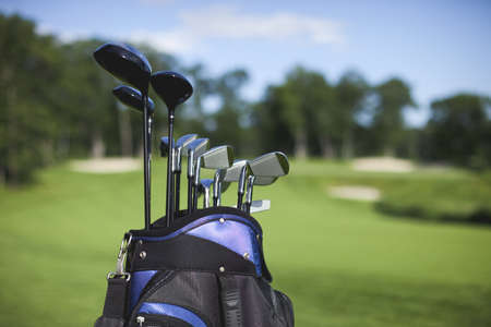 Blue and black golf bag and clubs against defocused golf course background