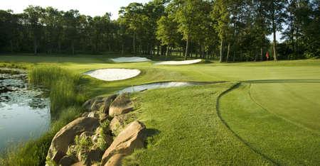 Golf grün mit Fallen, die von Felsen, Wasser und Bäumen gesäumt Standard-Bild - 17692236