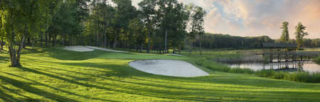 Golf green with white sand traps beside pond and bridge in panorama view