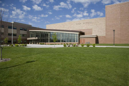 A modern high school showing the entrance on a sunny day with blue sky and clouds