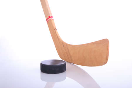 Hockey stick and puck on reflective surface with a white background