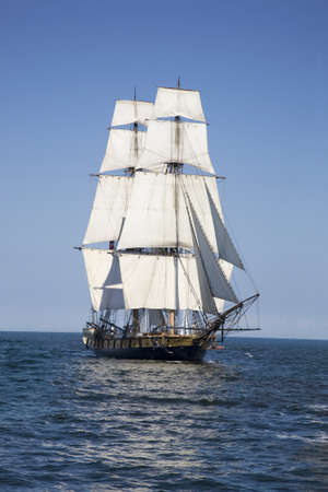 A tall ship known as a brigantine sails on blue water Фото со стока