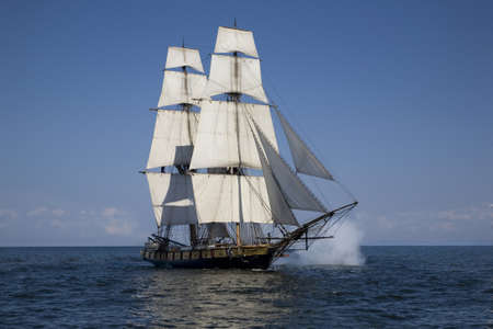 A tall ship known as a brigantine sails on blue waters with cannons firing