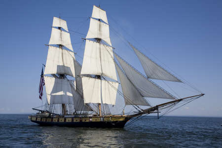 A tall ship known as a brigantine sails on blue water Banco de Imagens