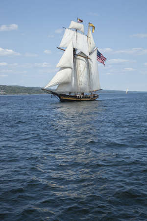 A tall ship known as a privateer sails on blue waters flying an American flag