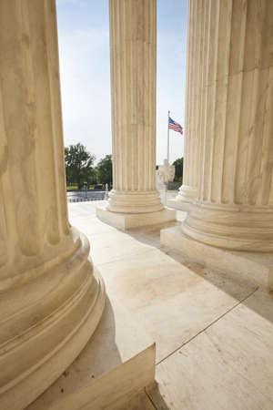 supreme court: American flag viewed between pillars of Supreme Court building in Washington DC Stock Photo