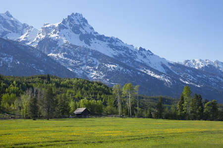 Barn and fence of horse ranch below the majestic Grand Teton mountains in Wyoming photo