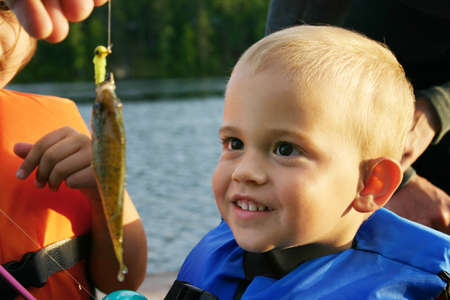 admires: A young boy admires the sunfish he caught off the dock at the lake