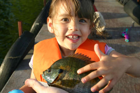 A young girl excitedly touches the first fish she has ever caught