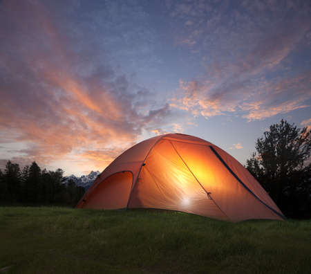 camping tent: An orange tent with a light glowing inside at dusk near the Grand Teton mountains Stock Photo