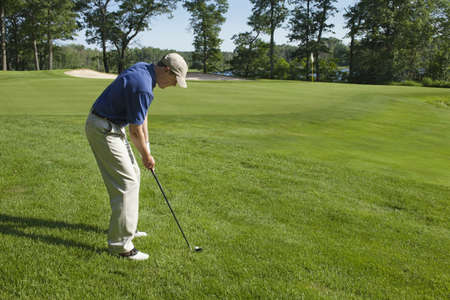 Golfer preparing to chip onto a green on sunny summer day