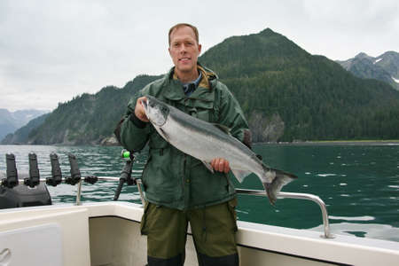 A happy fisherman in Alaska holds up a freshly caught silver salmon  photo