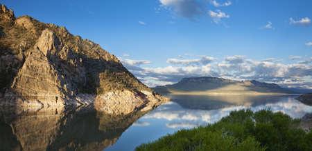 rocky point: Acqua calma del serbatoio Buffalo Bill nel Wyoming riflettendo un promontorio roccioso nella luce del mattino