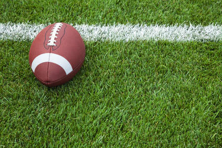 A college football at the goal line on a grass field