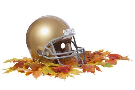 casco rojo: Un casco de fútbol americano del oro se sienta en un montón de hojas de arce colorido aislado en un fondo blanco