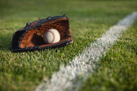 campo de beisbol: Un enfoque selectivo, ángulo de visión baja de un guante de béisbol y bola en el césped por una franja de campo