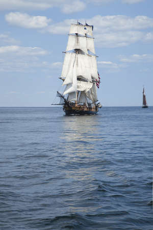 A tall ship known as a brigantine sails on blue water