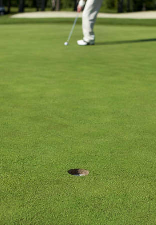 A golfer lines up a putt on a green  Focus on the hole