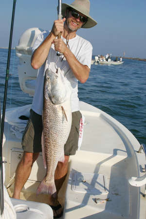 A happy fisherman holds up a big redfish caught off the Texas coast
