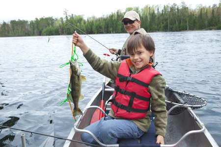 walleye: A young caucasian fisherman proudly holds up his first walleye of the day