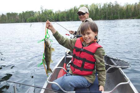 r boy: Un pescador caucásica joven sostiene con orgullo su primera lucioperca del día Foto de archivo