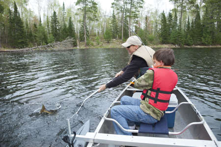 A young fisherman in a canoe catches a walleye