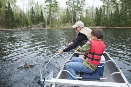 redes de pesca: Un joven pescador en una canoa coge un leucoma