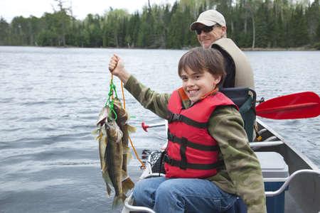 白人の若い漁師がロックオンのストリンガーを誇らしげに保持します。