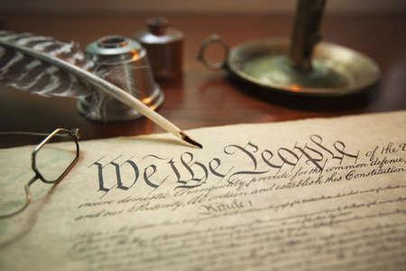 constitucion: Imagen de enfoque selectivo de la Constitución de Estados Unidos con la pluma, vasos y titular de la vela