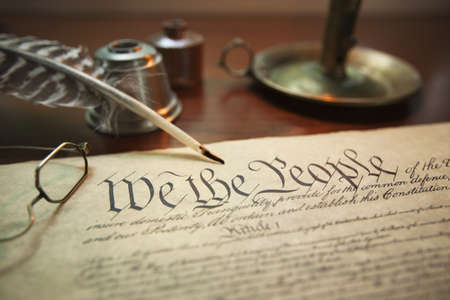 Selective focus image of the United States Constitution with quill pen, glasses and candle holder Stock Photo