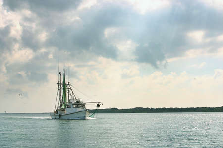 gulf: A shrimp boat on the gulf coast in Texas returns to port after a day of fishing Stock Photo