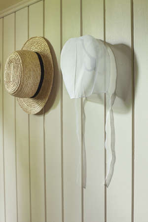 An Amish womans bonnet and a mans straw hat hanging on a wall Фото со стока