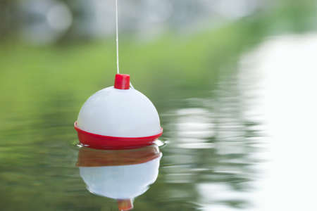A red and white bobber floats on water with ripples Stock Photo