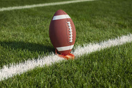 college football: A college football sits on a tee at a yard line ready for kickoff