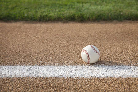 A baseball sits on a base path with grass infield
