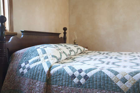 quilt: An old fashioned bed with a quilt alongside an oil lamp